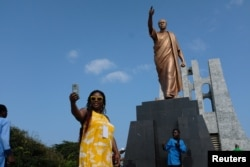 A member of a heritage tour group, traveling to Ghana to explore their ancestral roots, takes a selfie under the statue of Ghana's first president Kwame Nkrumah in Accra, August 7, 2019. Picture taken August 7, 2019. REUTERS/Francis Kokoroko