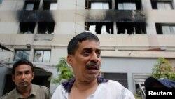 2013年5月8日,孟加拉国首都达卡的东海毛衣厂发生大火之后, 5月9日,制衣厂的一名负责人站在制衣厂的外面。