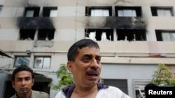 Seorang karyawan pabrik berdiri di depan sebuah pabrik pakaian yang terbakar di Dhaka (9/5). Pabrik yang terbakar tersebut milik Tung Hai Group, salah satu eksportir besar pakaian jadi di Bangladesh.