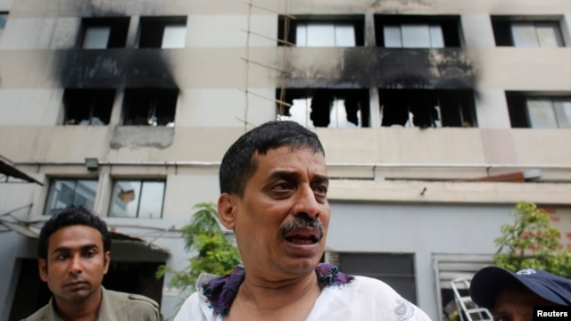 A company official stands in front of a factory belonging to Tung Hai Group, a large garment exporter, after a fire in Dhaka, May 9, 2013.