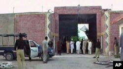 Police officers and people stand near a damaged jail gate after inmates escaped from the prison in the town of Bannu, Pakistan, in this still image taken from video, April 15, 2012.