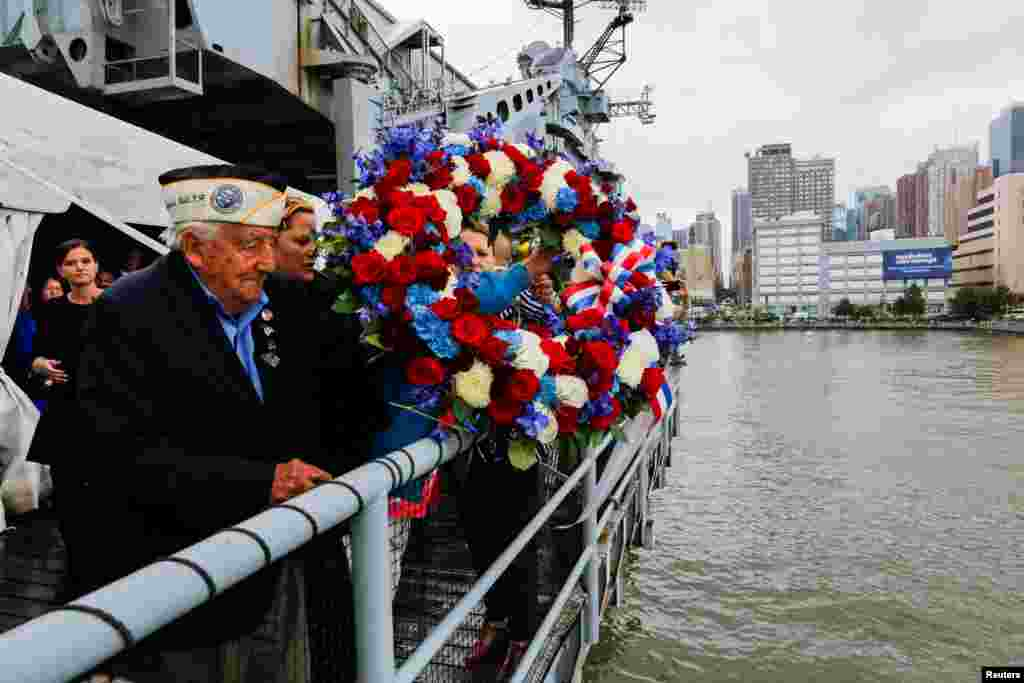 "World War II veteran and Pearl Harbor survivor Armando ""Chick"" Galella (L) tosses a floral wreath following an annual Memorial Day commemoration ceremony at the Intrepid museum in New York, May 29, 2017."