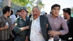A wounded man is assisted after gunmen stormed a courthouse in Mazar-i-Sharif, north of Kabul, Afghanistan, April, 9, 2015.