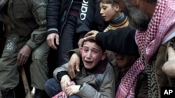 Ahmed, center, mourns his father Abdulaziz Abu Ahmed Khrer, who was killed by a Syrian Army sniper, during his funeral in Idlib, north Syria, Thursday, March 8, 2012.