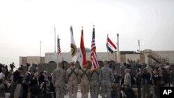 The US flag, Iraq flag, and the US Forces Iraq colors are seen before they are carried in during ceremonies marking the end of US military mission, December 15, 2011 in Baghdad, Iraq.