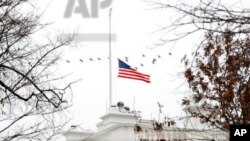 A flock of geese flies past an American flag at half-staff over the White House, Saturday, Dec. 1, 2018, in Washington. (AP Photo/Jacquelyn Martin)