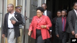 FILE: Joice Mujuru leaves the magistrates courts in Harare, Monday, Feb. 6, 2012, on the last day of the long awaited inquest hearing into the mysterious death of her husband Zimbabwe's former army General Solomon Mujuru. Mujuru died in a mysterious fire at his farm in 2011. Presiding magistrate Walter Chikwanha said the family submitted a request for the generals remains to be exhumed if the state evidence is inadequate. (AP Photo/Tsvangirayi Mukwazhi)