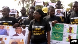 """FILE - Anti-slavery militants hold a banner whose message translates as """"No to slavery and racism, no to the regime of the general dictator Mohamed Ould Abdel Aziz"""" as they demonstrate, Aug. 3, 2016, in Dakar against the imprisonment of fellow activists in Mauritania."""