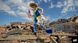 Susan Kates, warga setempat, berusaha menyelamatkan beberapa barangnya di antara reruntuhan rumahnya yang hancur akibat badai tornado di kota Moore, Oklahoma (22/5).