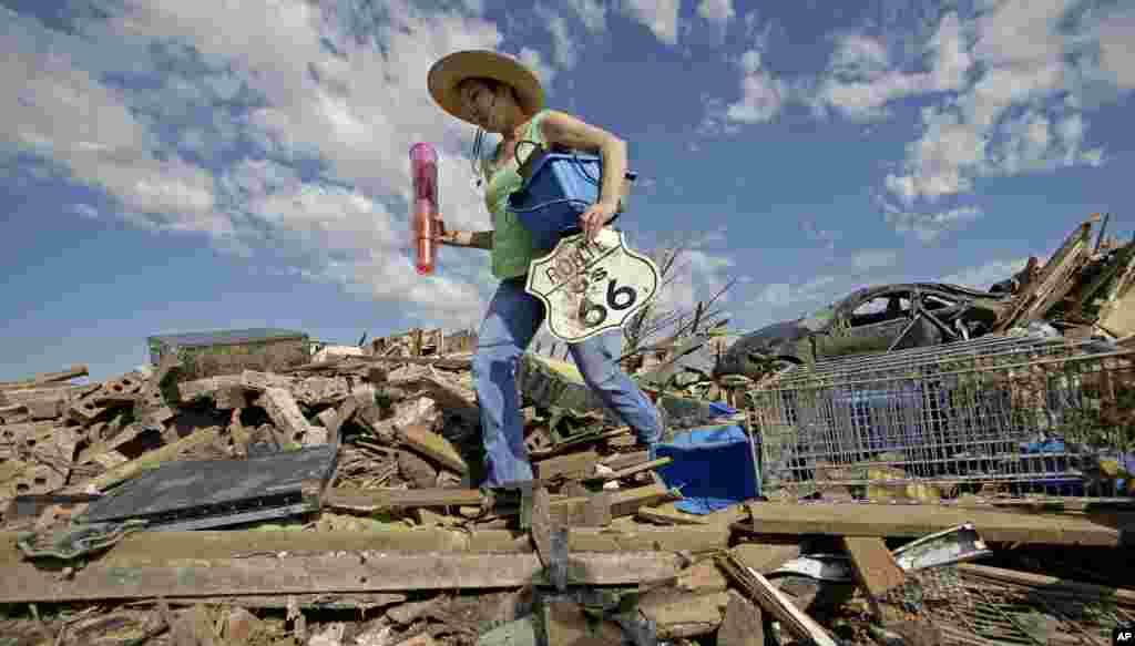 무어시의 수전 케이츠 씨가 토네이도로 파괴된 친구의 집에서 물건을 꺼내고 있다.