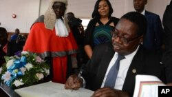 Newly elected Malawian president Peter Mutharika signs the oath book after he was sworn in, at the High Court in Blantyre, Malawi, May 31, 2014.