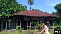 缅甸若开邦,一个女孩骑车从被烧毁的穆斯林屋子前经过。(美国之音朱诺拍摄,2013年11月13日)