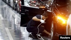FILE - An employee works on an assembly line producing Mercedes-Benz cars at a factory of Beijing Benz Automotive Co. (BBAC) in Beijing.