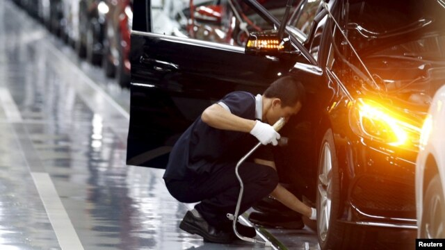 FILE - An employee works on an assembly line producing Mercedes-Benz cars at a factory of Beijing Benz Automotive Co. (BBAC) in Beijing. Observers say last month's PMI may have been affected by the annual Lunar New Year holiday, when factories traditionally shut down and workers return home.