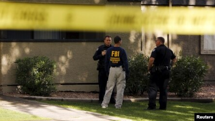 An investigator talks to police officers at  the Autumn Ridge apartment complex which had been searched by investigators in Phoenix, Arizona, May 4, 2015.