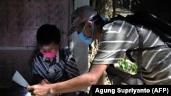 Guru SD Fransiscus Xaverius Fri Harna (kanan) mengajar di rumah siswanya di Magelang, Jawa Tengah, usai sekolah tutup akibat wabah virus Corona COVID-19. Beberapa guru mengambil medan berbahaya, cuaca buruk dan risiko tertular COVID-19, untuk menjangkau s