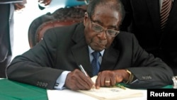 Zimbabwe President Robert Mugabe signs Zimbabwe's new constitution into law, Harare, May 22, 2013.