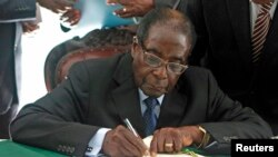 FILE - President Robert Mugabe signs Zimbabwe's new constitution into law in Harare, May 22, 2013.