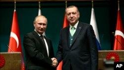 Presiden Turki Recep Tayyip Erdogan, kanan, berjabat tangan dengan Presiden Vladimir Putin, kiri, setelah konferensi pers bersama mengenai pertemuan mereka di Istana Kepresidenan di Ankara, 11 Desember 2017.