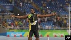 ທ້າວ Usain Bolt ຈາກ Jamaica ສະຫລອງໄຊຊະນະຫລຽນ ຄຳ ຫັລງຈາກການແລ່ນປ່ຽນໄມ້ 400 ແມັດຕໍ່ກັນສີ່ຄົນ.