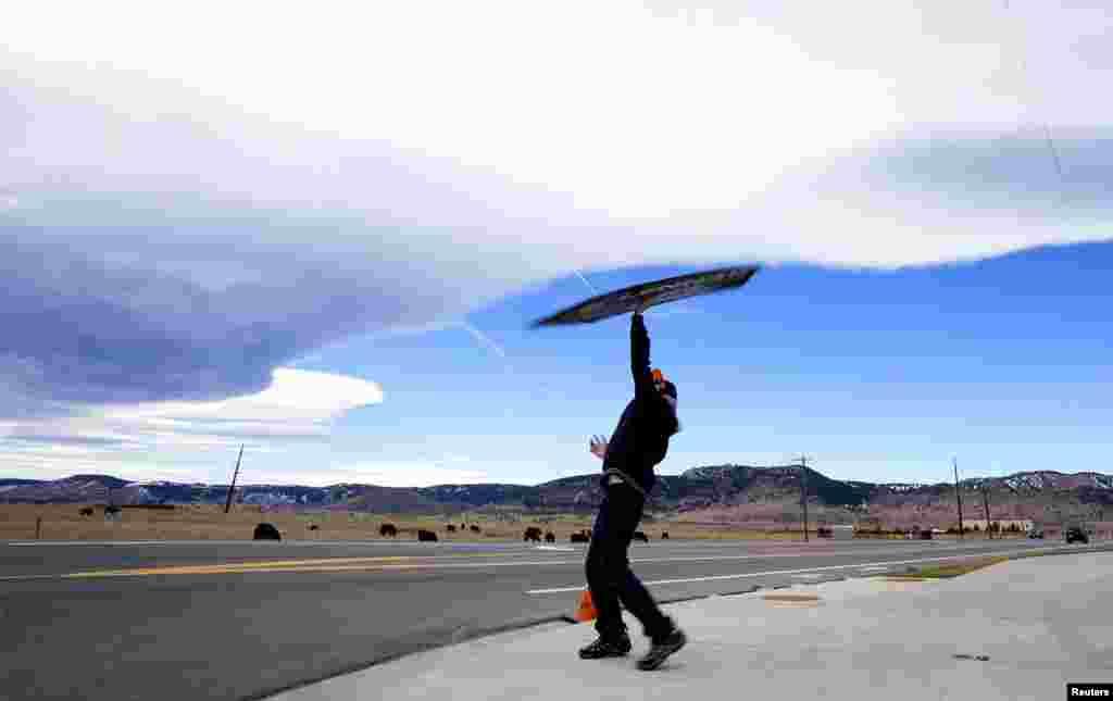Foster Glore ชายหนุ่มที่กำลังรับจ้างหมุนป้ายโฆษณาขายบ้านของ Lennar Homes ที่หน้าทางเข้าโครงการหมู่บ้านจัดสรรแห่งหนึ่ง ในเมือง Denver รัฐโคโลราโด