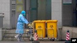身穿防護服的工人推著醫療垃圾的垃圾桶走過武漢醫療中心大門。(2020年1月22日)