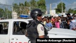 在海地首都太子港,海地國家警察守衛著美國大使館的入口。在總統莫伊斯遭暗殺身亡後,一些海地民眾聚集在美國大使館門口尋求庇護。(2021年7月9日)