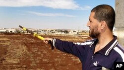 FILE - Free Syrian Army fighter, Bashar al Hajji, points towards the besieged Shi'ite village of Zahra in Aleppo, Oct. 17, 2012.