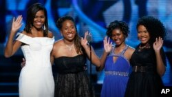 First Lady Michelle Obama, left, waves while standing on stage with Making A Difference award winners, from left, Kaya Thomas, Chental-Song Bembry and Gabrielle Jordan during a taping of the Black Girls Rock award ceremony at the New Jersey Performing Arts Center, March 28, 2015, in Newark.