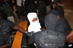 Security personnel surround former Chadian dictator Hissene Habre inside the court, in Dakar, Senegal, July 20, 2015.