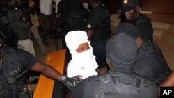 Para petugas keamanan memaksa Hissene Habre (tengah) tetap duduk di kursinya dalam pengadilan di Dakar, Senegal (foto: dok).