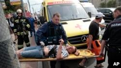 2014年7月15日,俄罗斯首都莫斯科地铁高峰期发生列车出轨事故后,医务人员和警察将一名受伤男子从一处地铁站抬出。