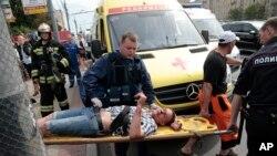 莫斯科地鐵發生列車出軌事故後,醫務人員和警察將一名受傷男子從一處地鐵站抬出