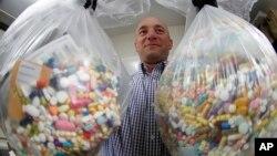 Detektif tindak pidana narkotika, Ben Hill, dari Kepolisian Baberton memperlihatkan obat-obatan opioid yang siap dimusnahkan, di Baberton, Ohio, 16 Oktober 2019. (Foto: Keith Srakocic/AP)