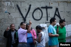 "People wait in line next to the word ""Vote"" spray painted on a wall before voting during the Constituent Assembly election in Caracas, Venezuela, July 30, 2017."