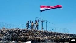 En esta foto de archivo del 17 de julio de 2018, publicada por la agencia oficial de noticias siria SANA, tropas sirias muestran un letrero de victoria junto a la bandera siria en Tell al-Haara, la colina más alta de la provincia suroccidental de Daraa, Siria. Israel derribó un avión de combate sirio que, según dijo, había roto su espacio aéreo el martes, cuando las fuerzas sirias llegaron a la frontera de los Altos del Golán por primera vez en siete años.