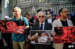 Participants hold pictures children during a protest of Turkish activists and Syrians living in Istanbul against the latest bombardment of Aleppo by the Syrian regime and its military allies, on Istiklal avenue in Istanbul, Oct. 1, 2016.