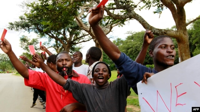 Roman Catholic priest Frank Bwalya (in red) and supporters hold red cards to display their displeasure with the government as they attend a rally in front of the National Assembly, in Lusaka, Zambia, March 22, 2011.