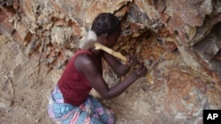 FILE - A woman rock-crusher hits rocks with a hammer in a quarry in Maroua, Cameroon, June 16, 2016.
