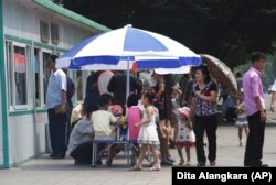 People line up to eat at a food kiosk in Pyongyang, North Korea.