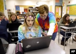 FILE — Teacher Carol Mowen, right, works with student Kirsten Delauney on an oral history project at Washington County Technical High School in Hagerstown, Md.