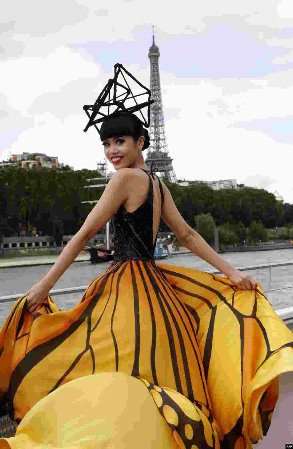 Vietnamese fashion show organizer, producer and model Jessica Minh Anh presents a creation during a fashion show on a tourist river boat cruising the Seine, as part of the J Autumn Fashion Show 2016 near the Eiffel Tower in Paris.