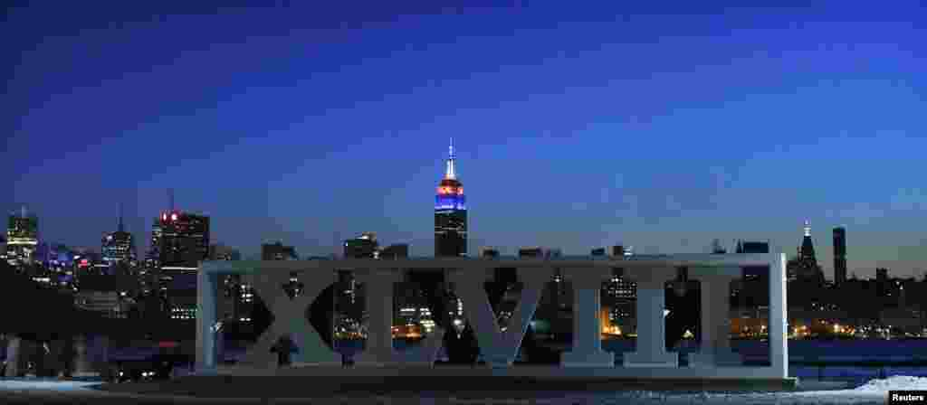 The New York skyline and the Empire State Building are seen in the distance as roman numerals for NFL Super Bowl XLVIII football game are displayed in Hoboken, New Jersey, Jan. 30, 2014.