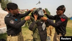 A technician from Pakistan's top bomb disposal unit is helped into his protective suit during a demonstration at the unit's headquarters in Peshawar, Sept. 12, 2013.