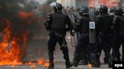 Des policiers congolais battent en retraite devant un cocktail Molotov à la périphérie de Kinshasa, République démocratique du Congo, 25 juillet 2006. EPA / NIC Bothma