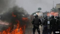 Des policiers congolais battent en retraite devant un cocktail Molotov lancé en leur direction à la périphérie de Kinshasa, République Démocratique du Congo, 25 juillet 2006. EPA / NIC Bothma