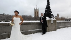 How not to dress for the cold: a newly married couple poses for a photograph opposite the Houses of Parliament in London on Saturday. Snow brought much of Britain to a standstill.