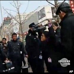 何宗安高举双手抗议被警察推挤的镜头(照片中右侧带眼镜的女记者)