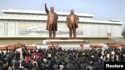 북한 평양 만수대 언덕의 김일성, 김정일 동상. 주민들이 꽃을 바치고 절을 하고 있다. (자료사진)