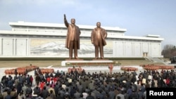 North Koreans place flowers before the statues of North Korean founder Kim Il-sung (L) and his son, late leader Kim Jong-il, on the 101st anniversary of the elder Kim's birth in Pyongyang, April 15, 2013. (KCNA)